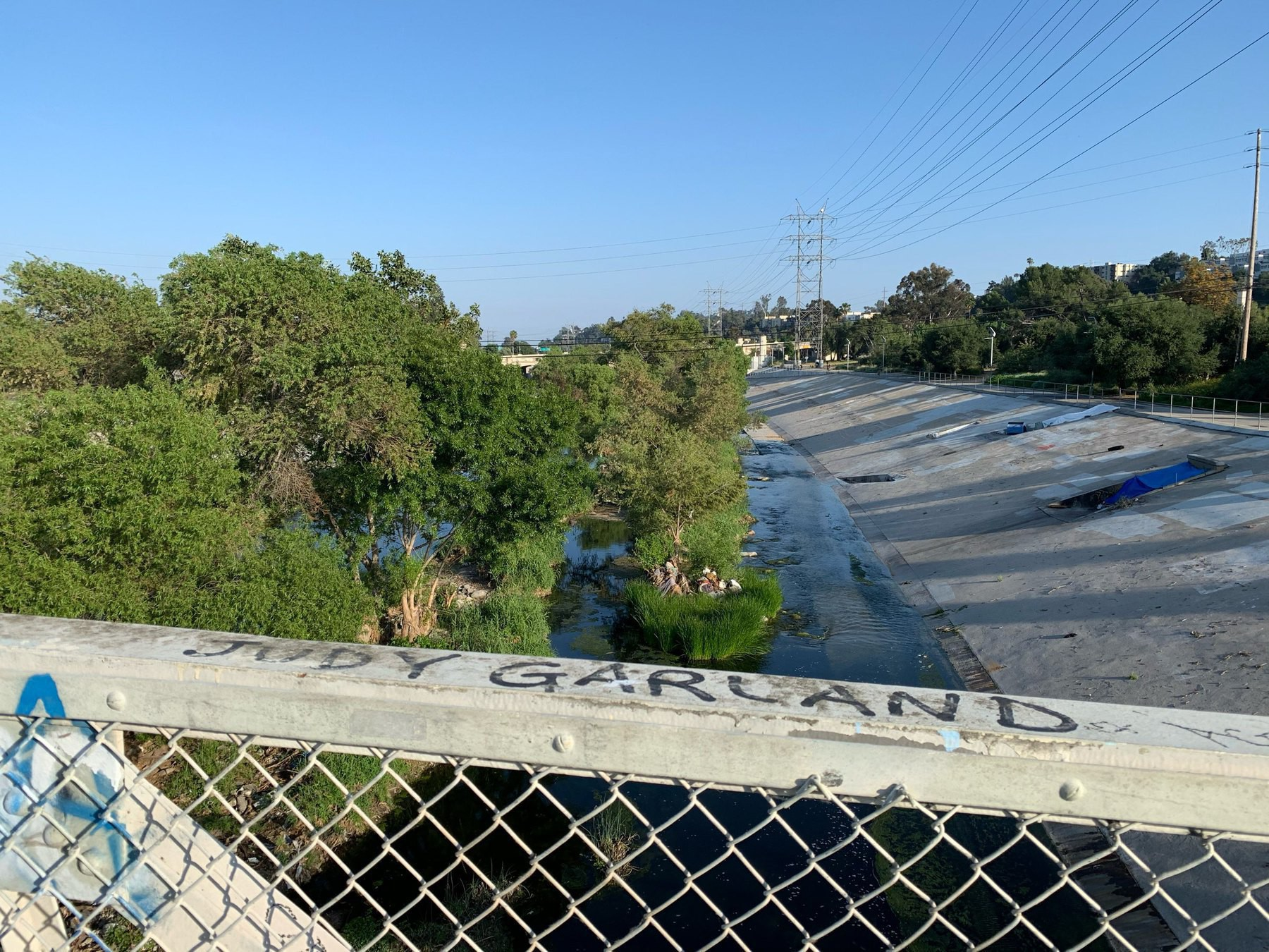 overlooking bridfe railing with Judy Garland written on it with wide blue sky and green trees in the LA river below